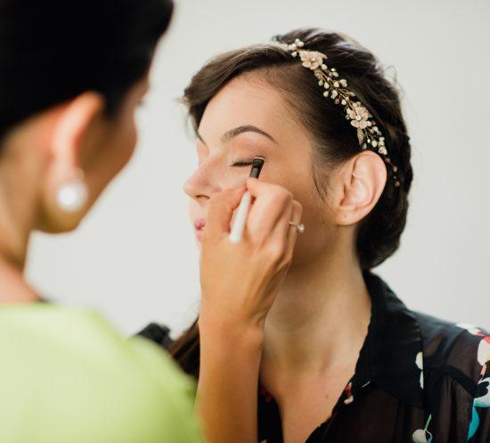 poza makeup artist care machiaza o mireasa