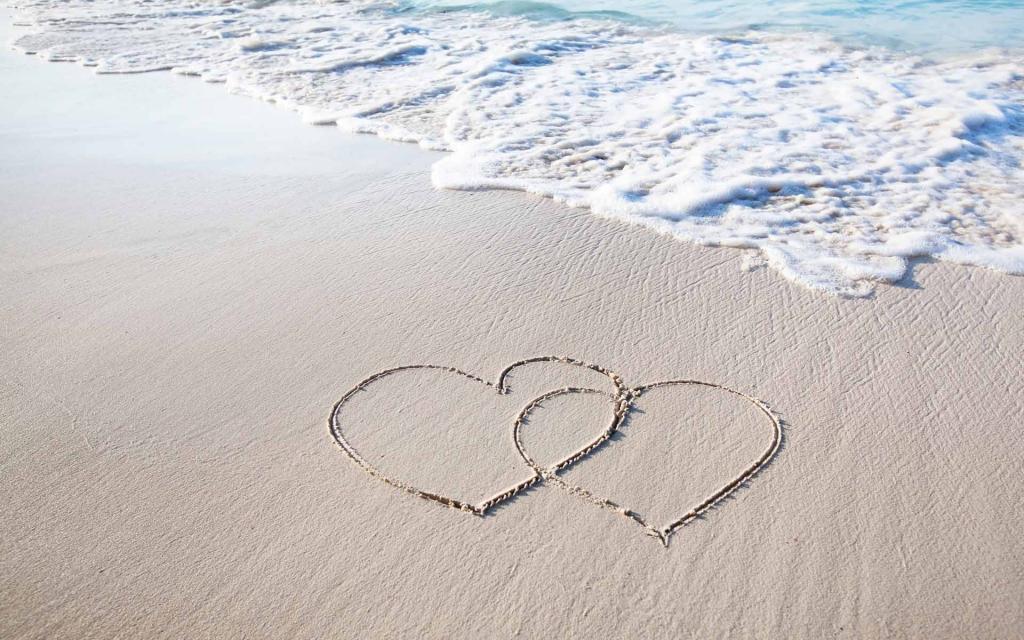 inimi desenate pe nisip la mare
